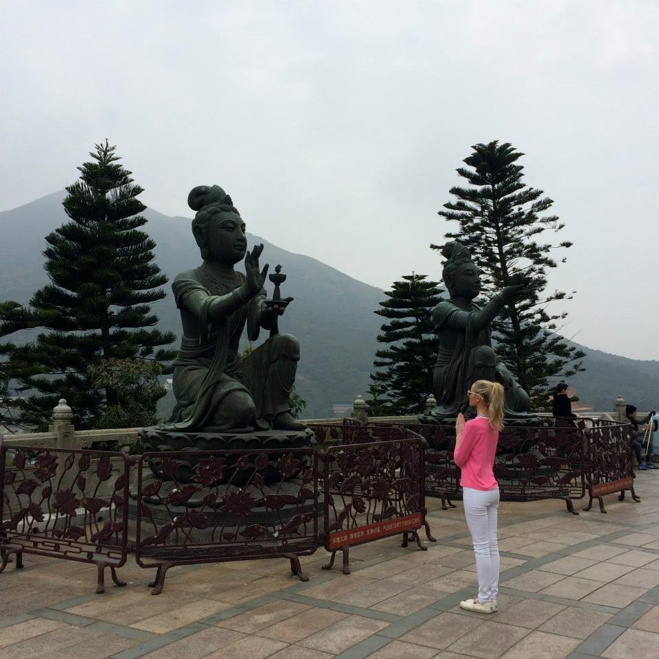 Travel Blogger Katy Johnson praying to Buddha.