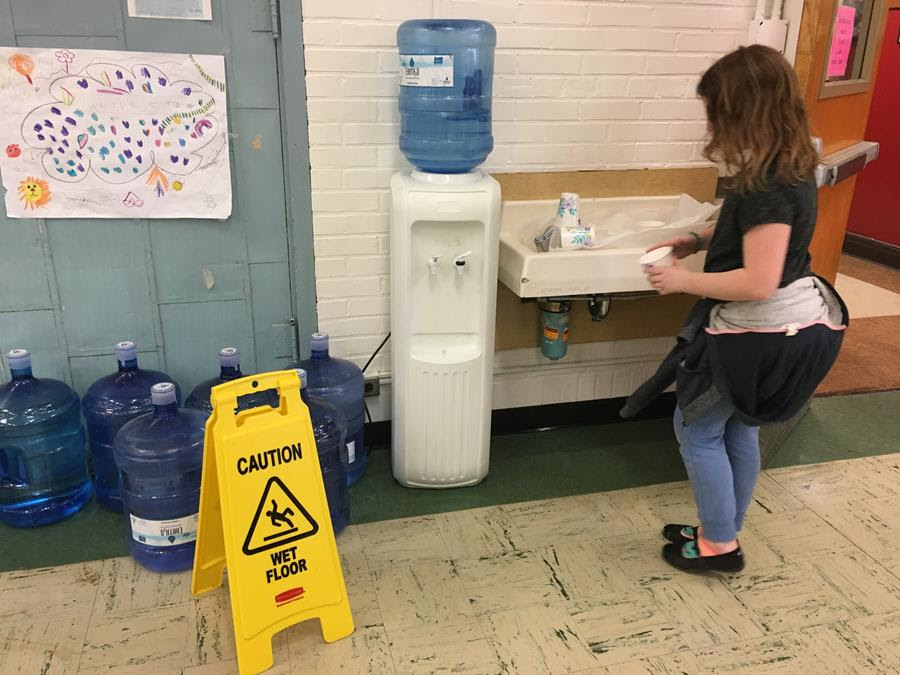A Photo of a James John Student in front of a broken water fountain.