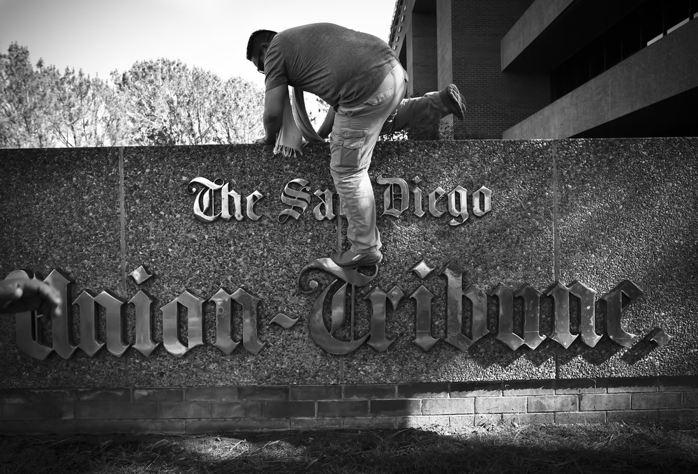 After 43 years in the same location, The San Diego Union-Tribune newspaper moves from its building in Mission Valley to new offices in downtown San Diego. Here photographer Alejandro Tamayo climbs down from the sign in front of the building shortly after the photography staff took a going-away group photo there.