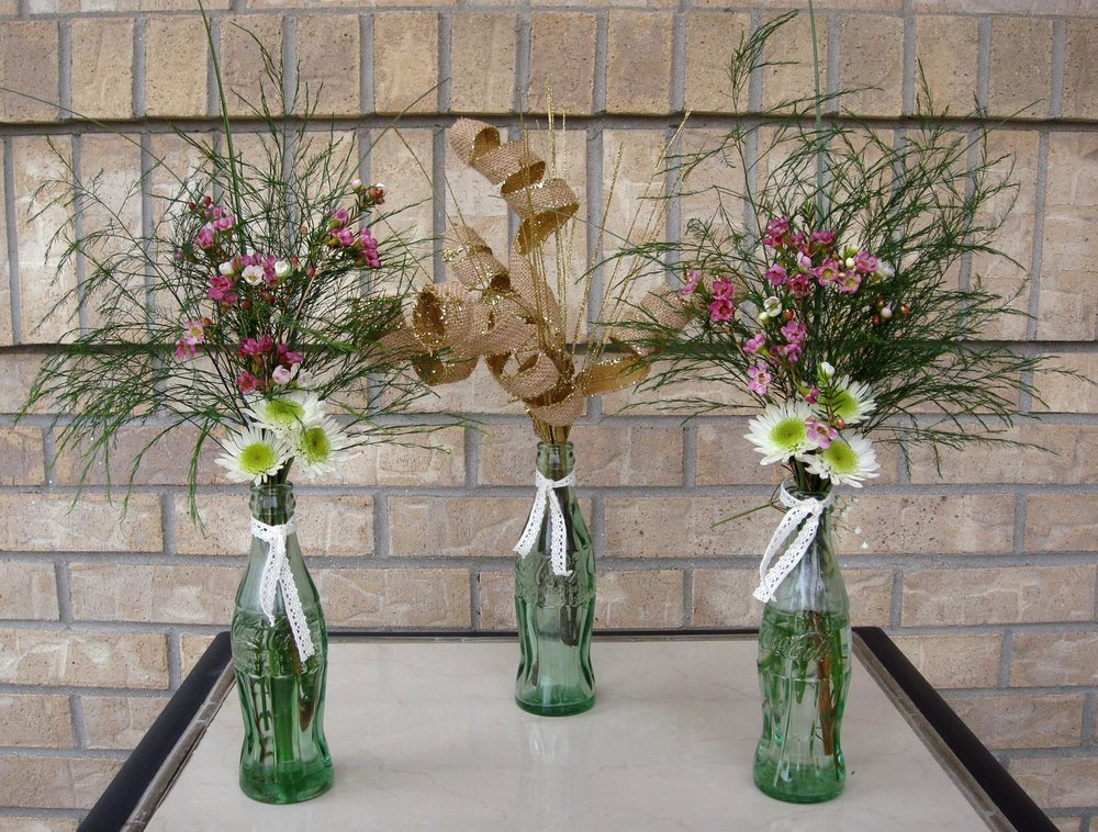 table centerpiece / reception decor - fresh flowers, Coke bottles, burlap curls