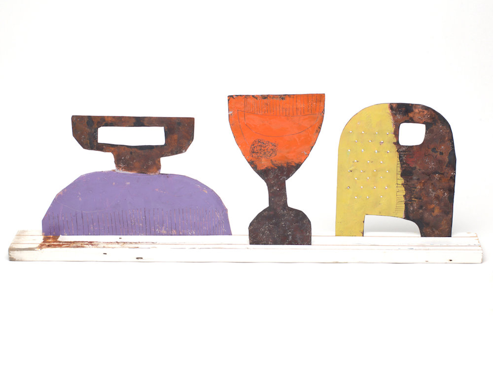 Family 2 Large fork - Purple front / pink back Large fork - Orange front / White back Large cheese grater - Yellow front / light blue back On a large re-purposed white picket fence Copper, paint and enamel 660 x 240 mm