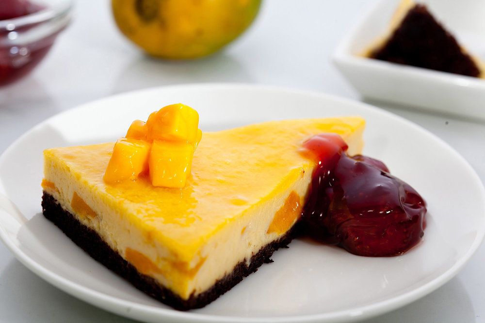 Mango Brownie Cheesecake  - Did you know cheesecake may have been created on the Greek island of ancient Samos? Cheese mold as old as 2000 BC was excavated by anthropologists on the island leading one to believe that cheese was in full-fledged production at the time. We've got the regular and the seasonal together to create a belter of a dessert.A rich, chocolatey slab of brownie bears a creamy mango cheesecake riddled with diced mango. A delicate glaze of mango pulp with a spoonful of cherry compote by the side completes this celebration of mangoes and chocolate.