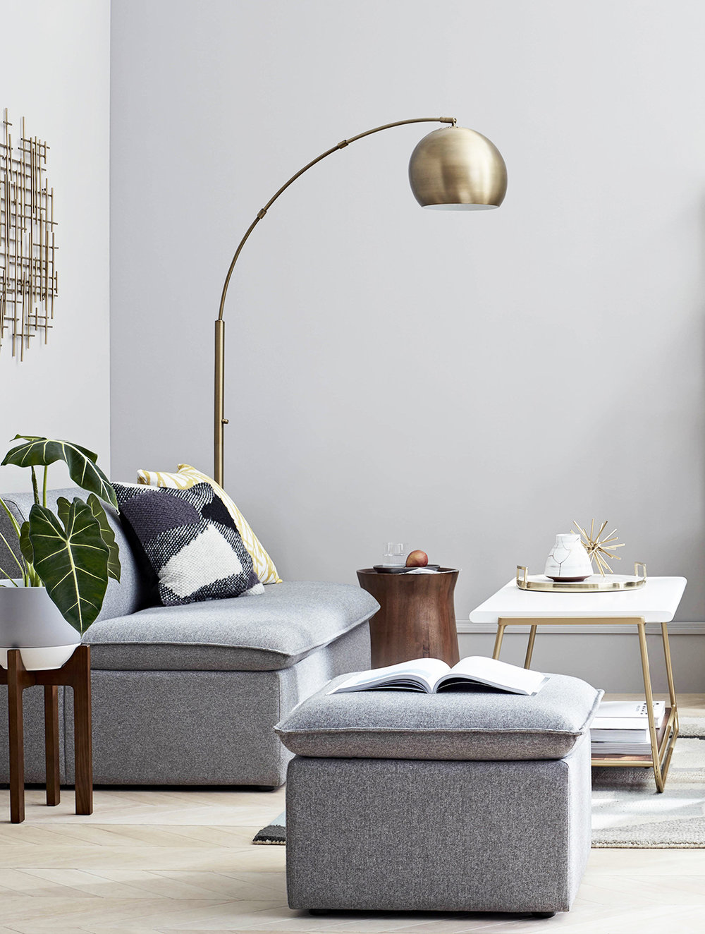 Grey modular sofa and ottoman, Arc Globe floor lamp, Sayer coffee table.