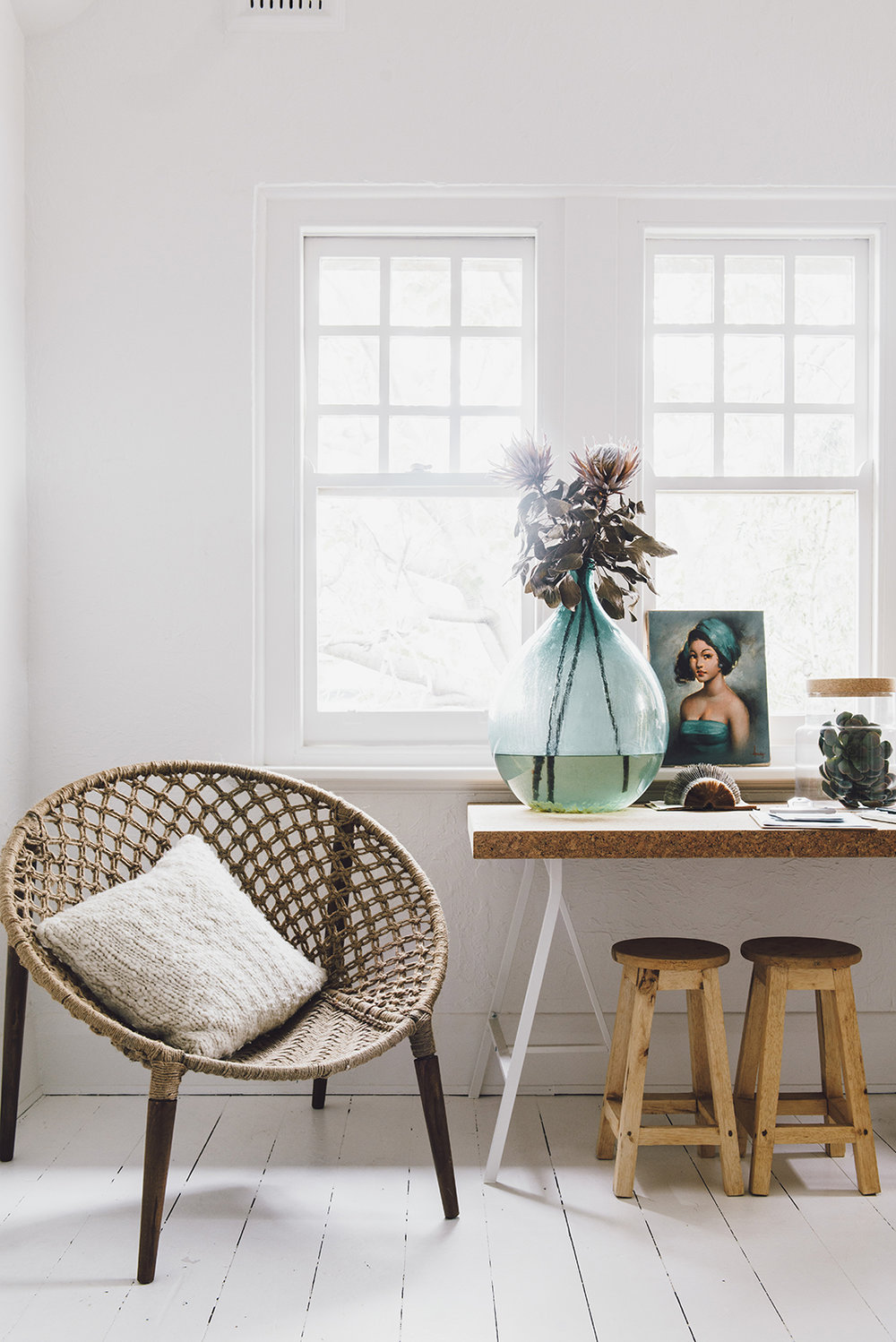 The woven string chair is modern but references '50s/'60s style. The fabulous aqua glass jar – a flea-market find – makes a color-perfect vignette with the portrait. The trestle table with its cork top and the natural timber stools are well-priced pieces.