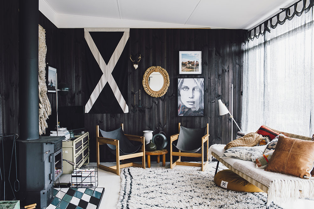 The angled lamp, shag carpet and kilim-covered cushions say modernist, but in a casual way. Special pieces include a vintage tribal mirror from Etsy France and two linen swing chairs. The showstopper is the stained black timber wall (using stain instead of paint lets some of the grain show through).