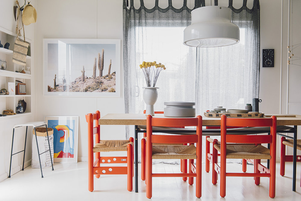 Fabulous tangerine-colored Italian designer chairs contrast with a cork-top table from a collection that English designer  Ilse Crawford  did in collaboration with IKEA.