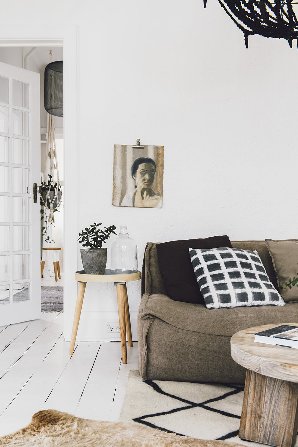 The unframed artwork is just pinned on the wall, and the rustic table and textured grey planter are easy-going accessories. White walls and white floors in this art deco apartment create a cocoon for the stylist-owner's signature collection of casual sofas, old-world artworks, vases and collectables.