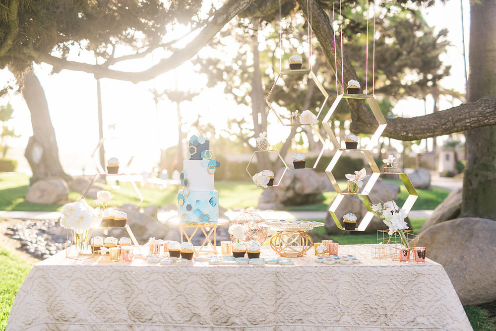 The cake and dessert table is such a special feature with a metal hexagon hanging shelf with floating cupcakes and flowers and delicate blue and metallic cookies. The cake by Cute Cakes is a brilliant fit!