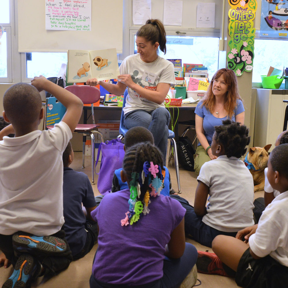 Program Leader Sarah conducts a read aloud of  Unlovable  to a group of SitStayRead first grade students at Bond Elementary. (D. Sutton)