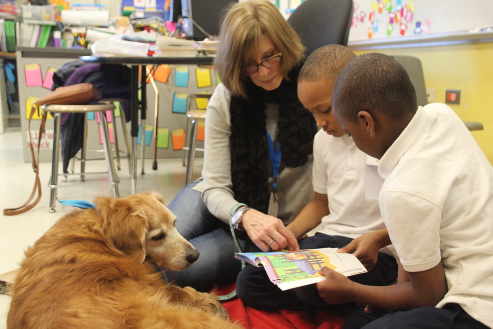 Ms. Betsy and her Certified Reading Assistance Dog, Bella, work with two second-grade students at Brunson Elementary in the Tail Blazers program.