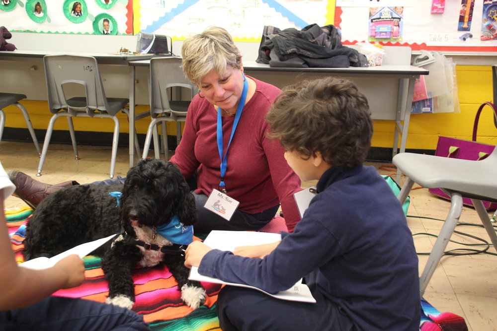 Second-grader Javon reads out loud to Dog Team Ms. Sue and Macy in a Tail Blazers program.