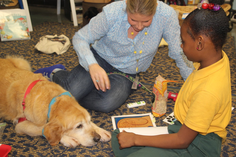 Dog Team Ms. Gina and Daisy listen to a third-grade student read poetry out loud in a Poetry Pals program.