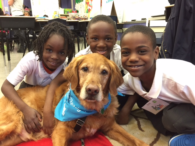 Second-graders Eric, Malik, and Zarion pose with Certified Reading Assistance Dog, Deacon, after reading to him in their Tail Blazers program.