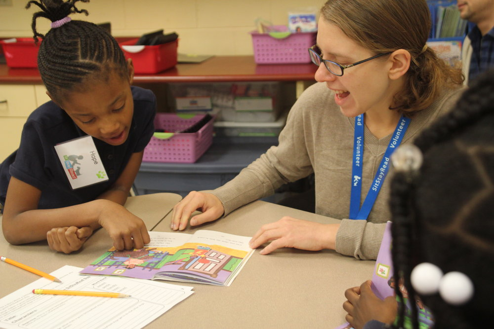 Book Buddy volunteer Amanda works with a second-grade student on their reading skills in a Tail Blazers program. (M. OBrien)