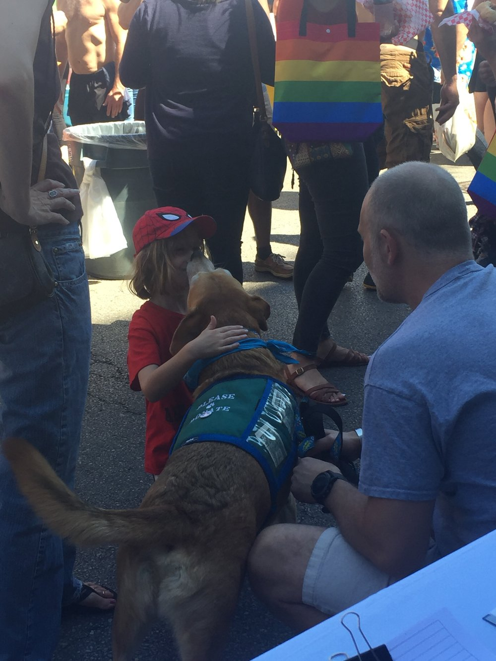 Certified Reading Assistance Dog, Cosi, gives kisses to his new, little friend at Market Days on Saturday. (V. Luisi)