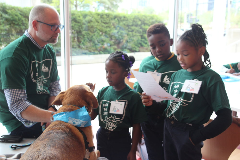 Blakenship listens to stories as his Certified Reading Assistance Dog, Cosi, receives pets. (M. OBrien)