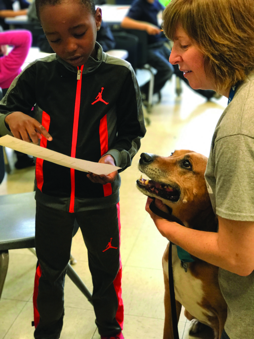 Certified Reading Assistance Dog Buster listens to a first-grade student's story in a Little Buddies program. (K. Love)