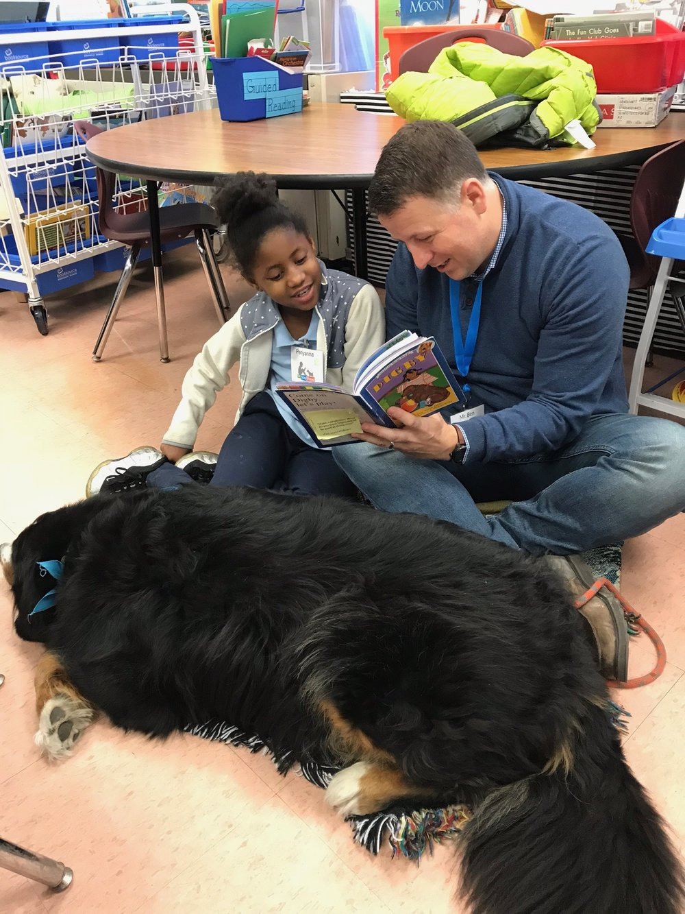 Board Member and Dog Team volunteer Ben reading with a second grade student while Certified Reading Assistance Dog Hank sleeps and waits for pets during a SitStayRead Tail Blazers program.