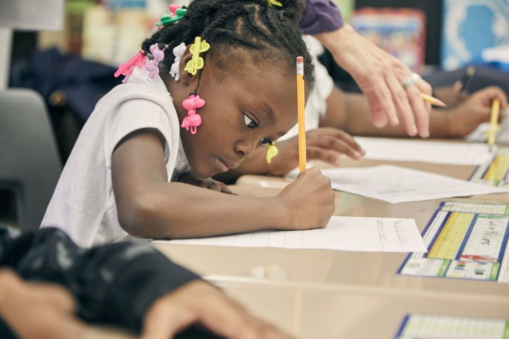 Second-grader Trinity works on her story during a SitStayRead Tail Blazers program at Hughes Elementary.