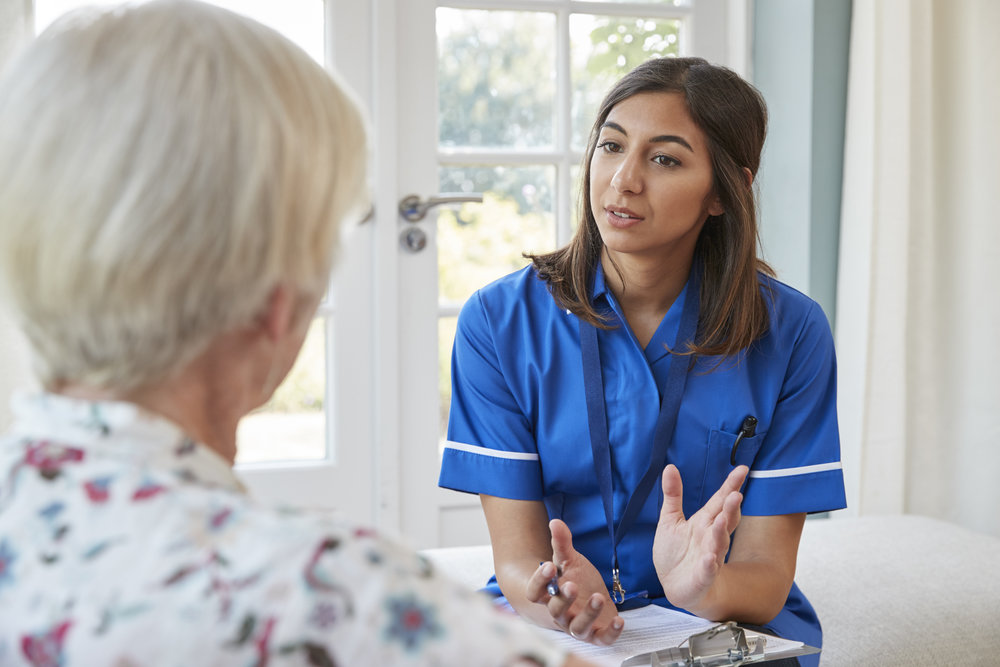senior-woman-talking-to-young-care-nurse-on-home-P3MELDH.jpg