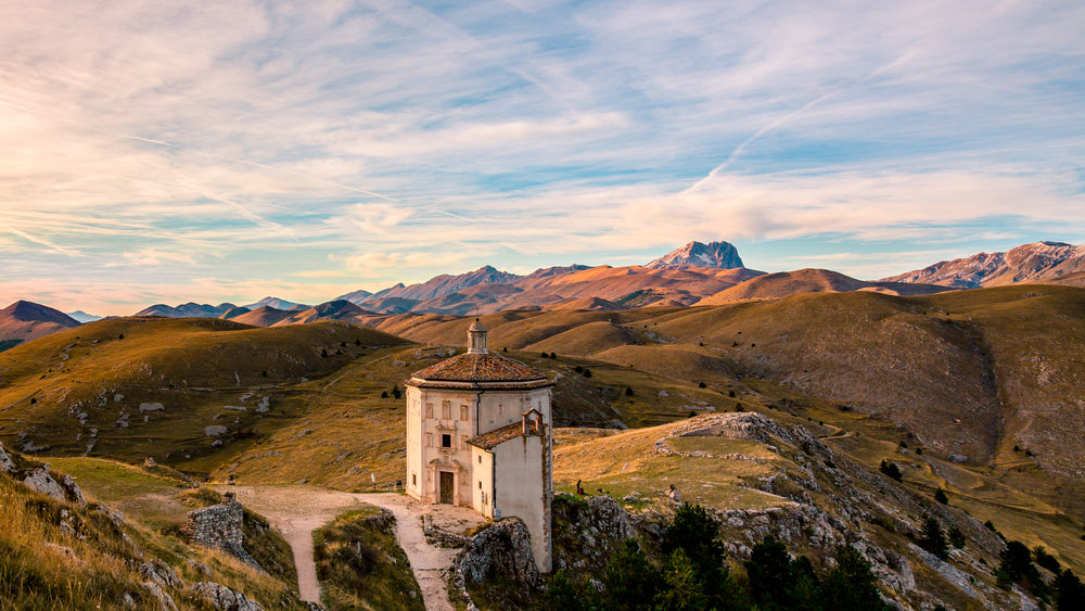 The devastatingly beautiful Italian Autumn means big sweatshirts and gloves, packing lunch, and heading into the mountains. Here, a red-sweatered vacationer enjoys the sunset in Abruzzo, the sun peeking through a thick layer of clouds on the western mountain horizon.