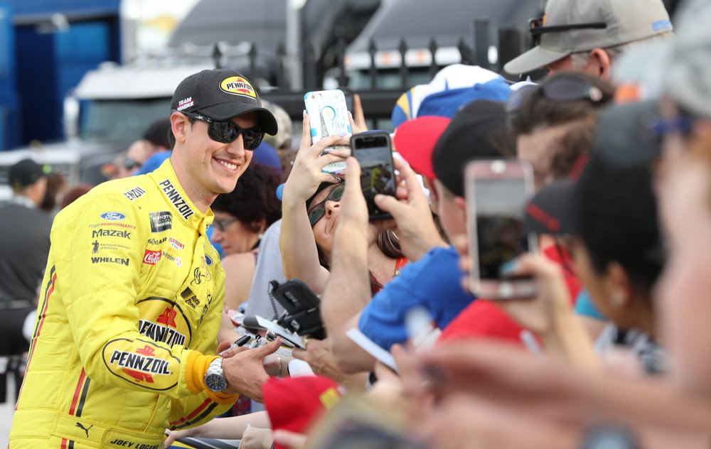 Joey Logano taking a selfie with a fan before the race.