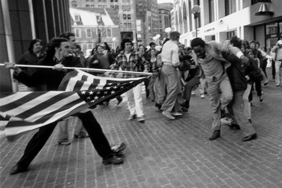"""The Soiling of Old Glory"" , City Hall Plaza, Boston, April 5, 1976; photo by Stanley Forman, Boston Herald American; book by Louis Masur."