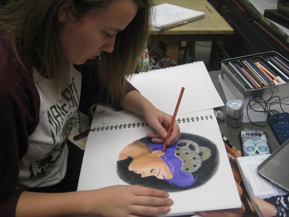 Karoline working in Prismacolor pencils on drawing she created in  Open Workshop.