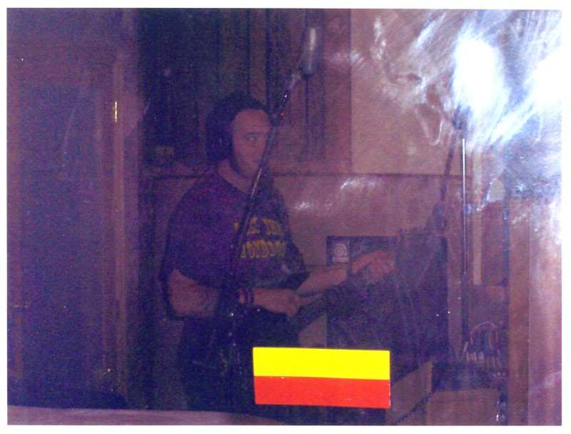 Ghost in the Machine The famous photo of the ghost. Here the bassist from Drown Mary is visited during a recording session in the live room. The yellow and red stripes on the bottom of the shot are taped markers on the glass door through which the photo is taken.