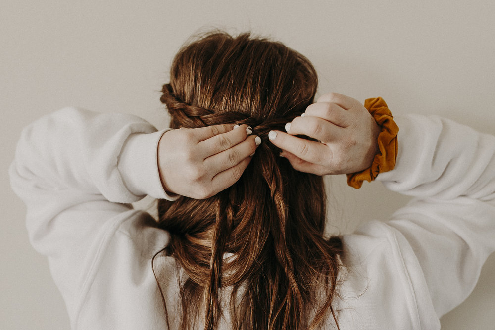 """Lastly, is my go-to travel hairdo—the half-up crown braid. This style is so easy to do, looks great with frizzy, curly, or straight hair, and stays in place all day long!    To create this look, I simply start a dutch braid on each side of my part, and add hair only to the front strand, as I go—stopping when I reach my ear. Then I continue the braids until they meet at the back of my head, pin into place, then """"pancake"""" them (or pull them apart a bit)to get a fuller look."""
