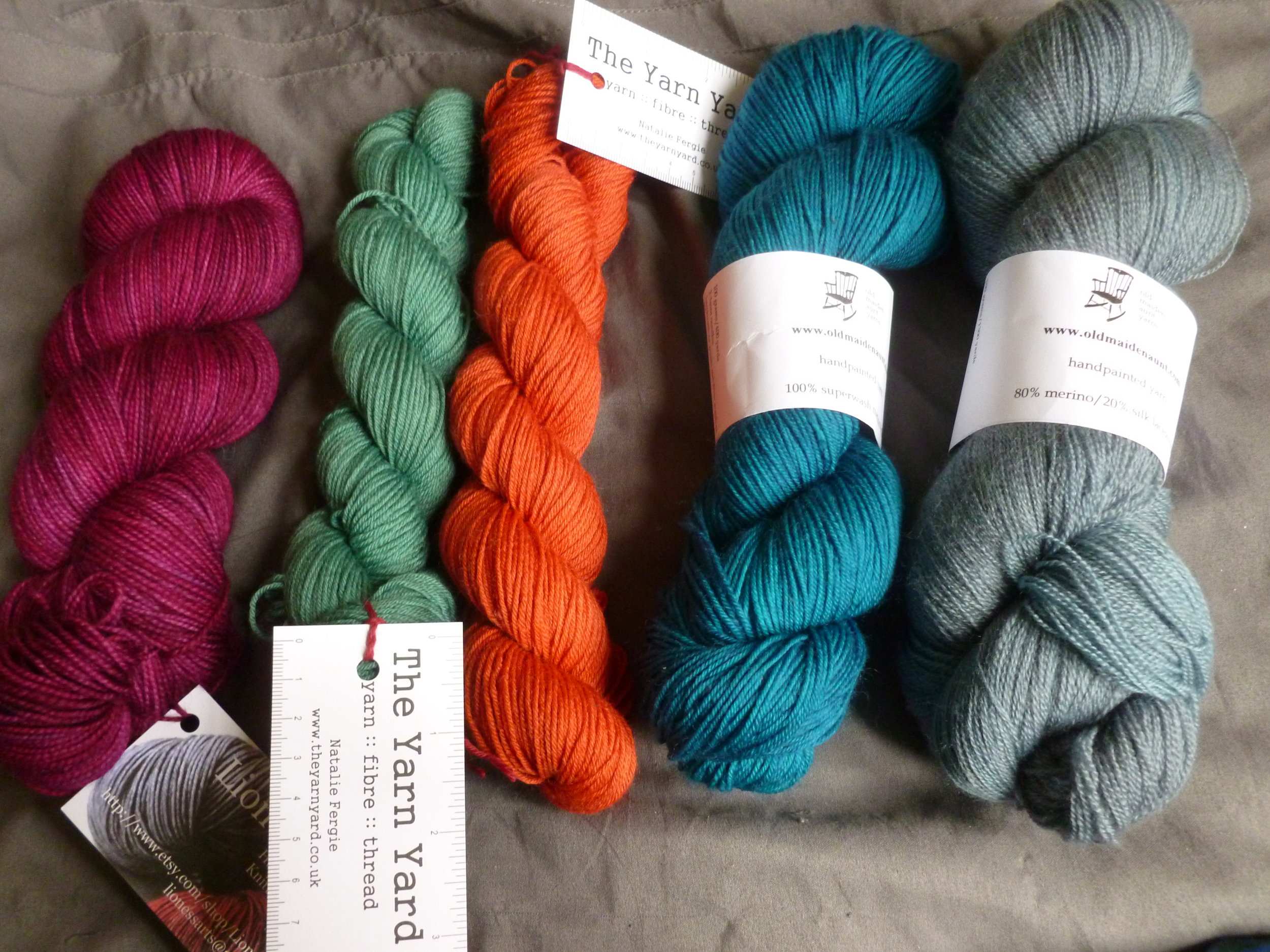 Victorious spoils of war! L-R: Lioness Yarns King of the Jungle Sock, 'Thoughts'; The Yarn Yard BFL (2 skeins, green and orange); Old Maiden Aunt 100% merino 4-ply, 'Seen the Ocean'; Old Maiden Aunt 80% merino/20% silk laceweight, 'Moody.'
