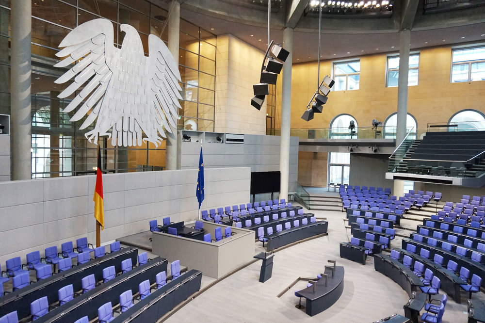 "The big, fat hen bearing the symbol of the German Bundestag amidst a sea of ""Reichstag blue"" seats specially designed for the German Parliament"