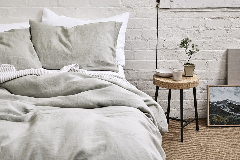 Linen Duvet Cover and Pillowslips in Stone with the Linen Fitted Sheet and Pillowslips in White and the Linen Flat Sheet in Stripe from  In Bed . Photo by Terence Chin, styling by Imogene Roache.