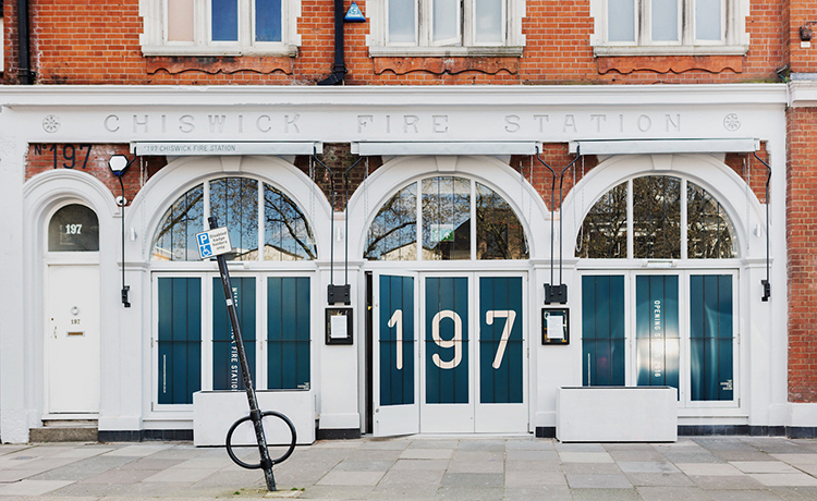 The entry presents a powerful contrast to the original façade, with the original fire station red brickwork and lettering still intact.