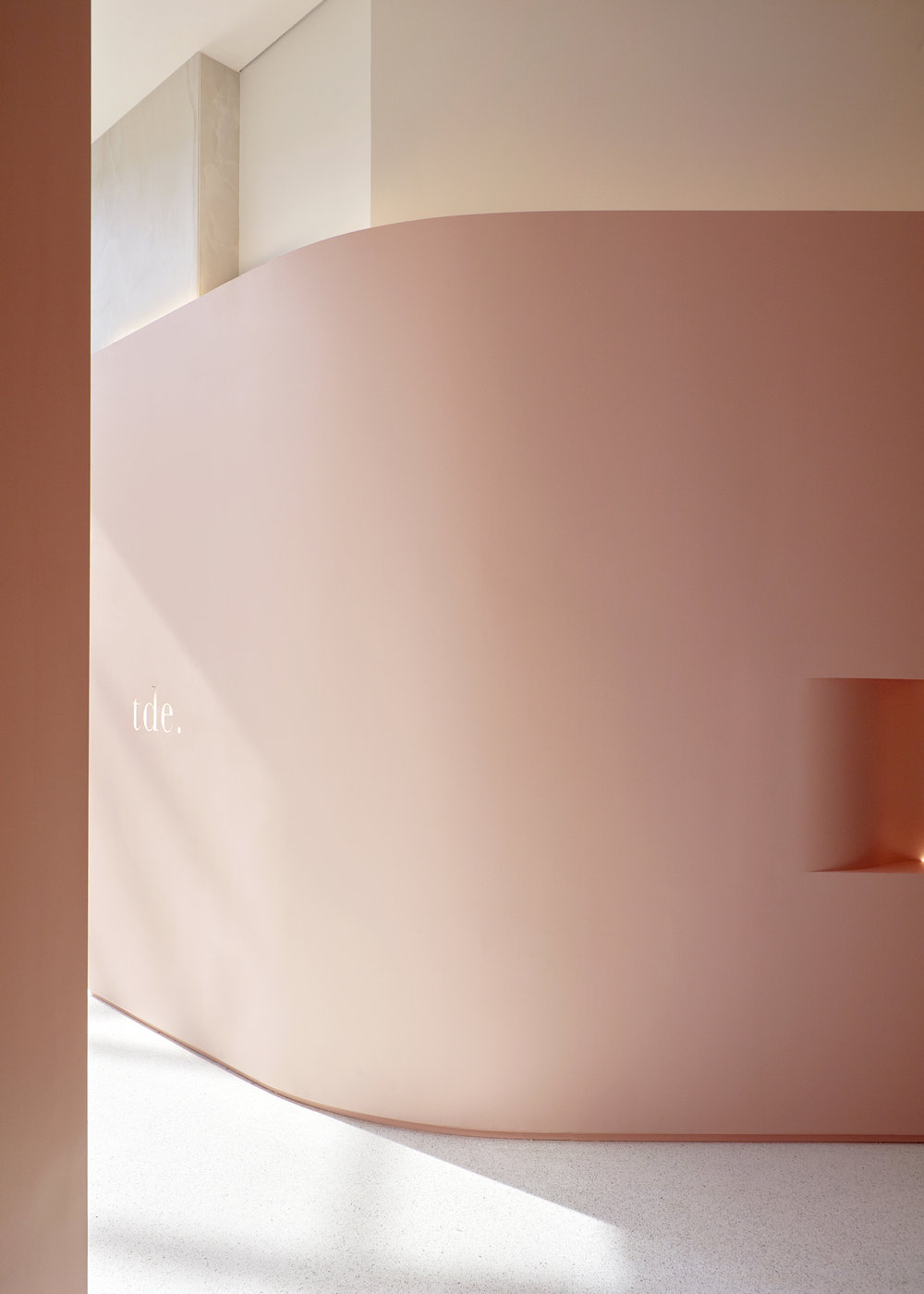 A sweeping pastel pink curve wraps the interior from the entry, around the four walls of the store.
