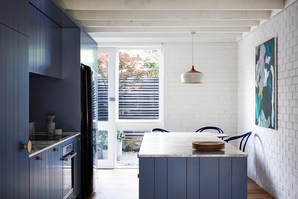 Marble-topped kitchen benches and bold, blue-paneled joinery featuring blonde-wood handles from  IN-ERTIA . Photo - Caitlin Mills. Styling - Tamara Maynes.