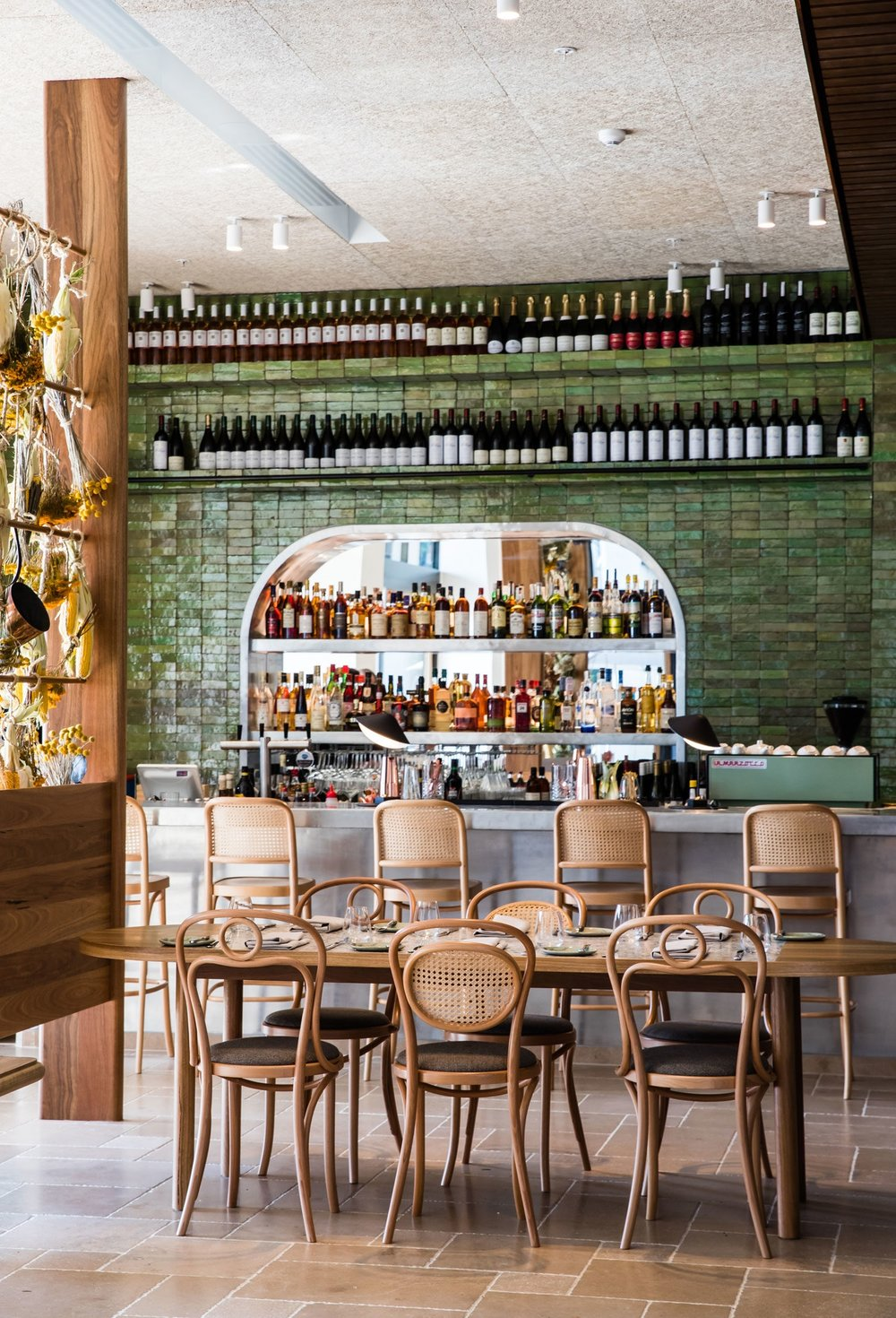 The bar at  Été Restaurant  is framed with hand-made green ceramic tiles and clad with hand-beaten zinc.
