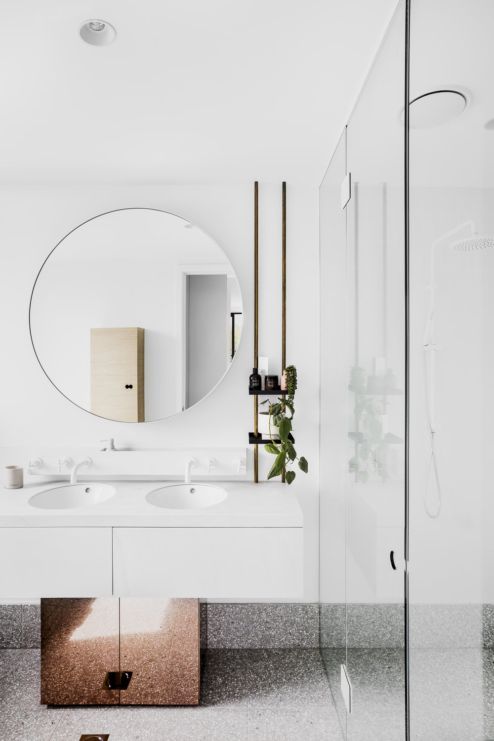 Finishes have aspects of reflectivity and neutrality including white walls, white tiles and light grey terrazzo flooring in the bathrooms. Photo -  Maegan Brown .