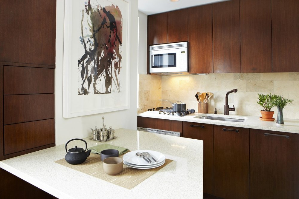Custom kitchen cabinetry in walnut takes advantage of the entire height of the space.