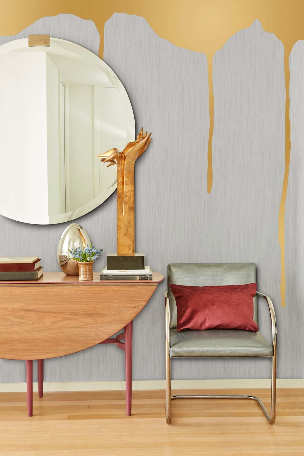 wooden table with single couch, big round mirror hanging on the painted wall