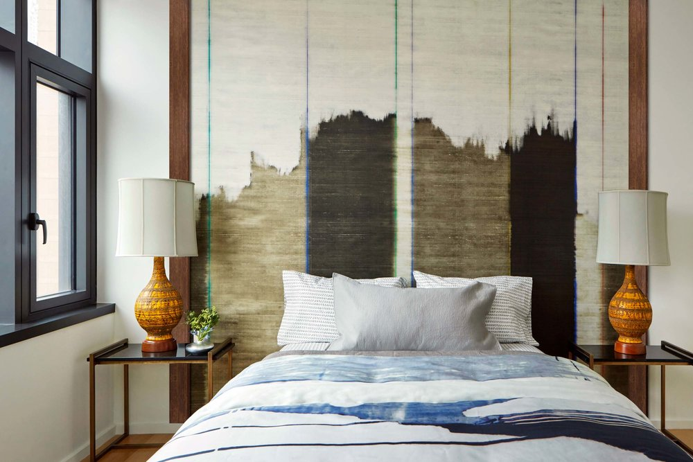 stylish painted bedroom with two white night lamps on each side of the bed