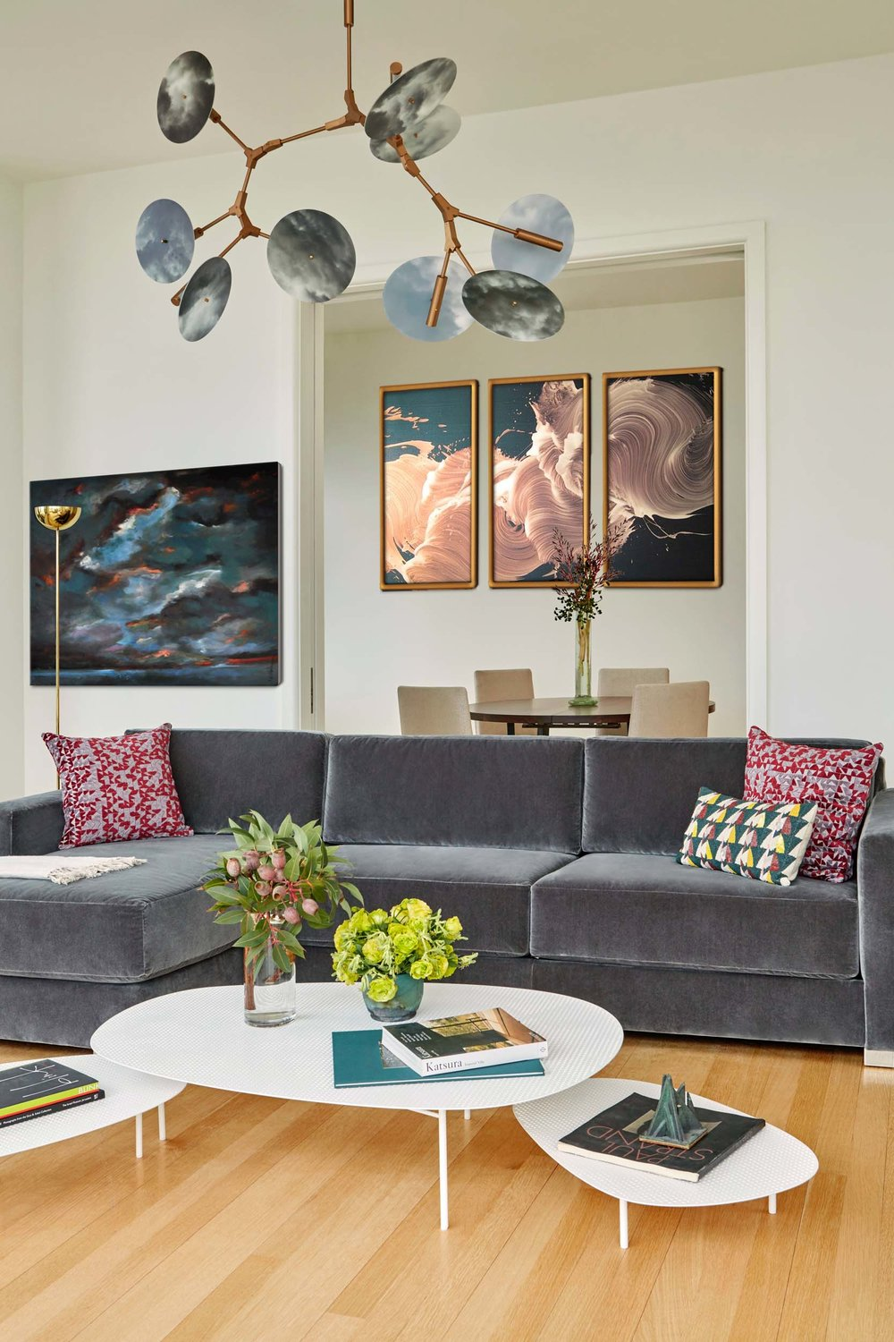 modern design living room with round table for four behind the large sofa,paintings hanging on the white painted wall and stylish decoration on the ceiling