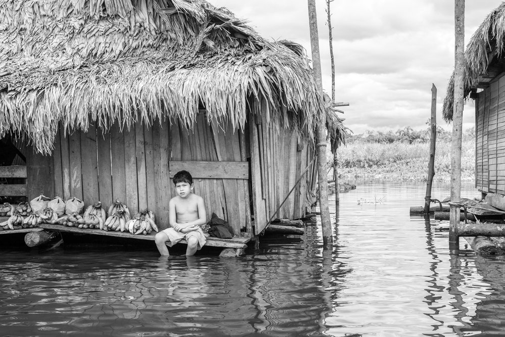 A young boy sells bananas in the flooded village of Belen in Iquitos, Peru.