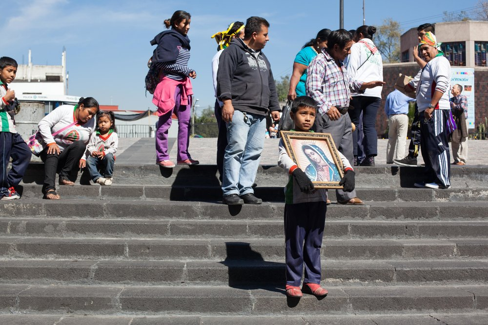 A young boy holds a picture of the the Basilica of Our Lady of Guadalupe in Mexico City