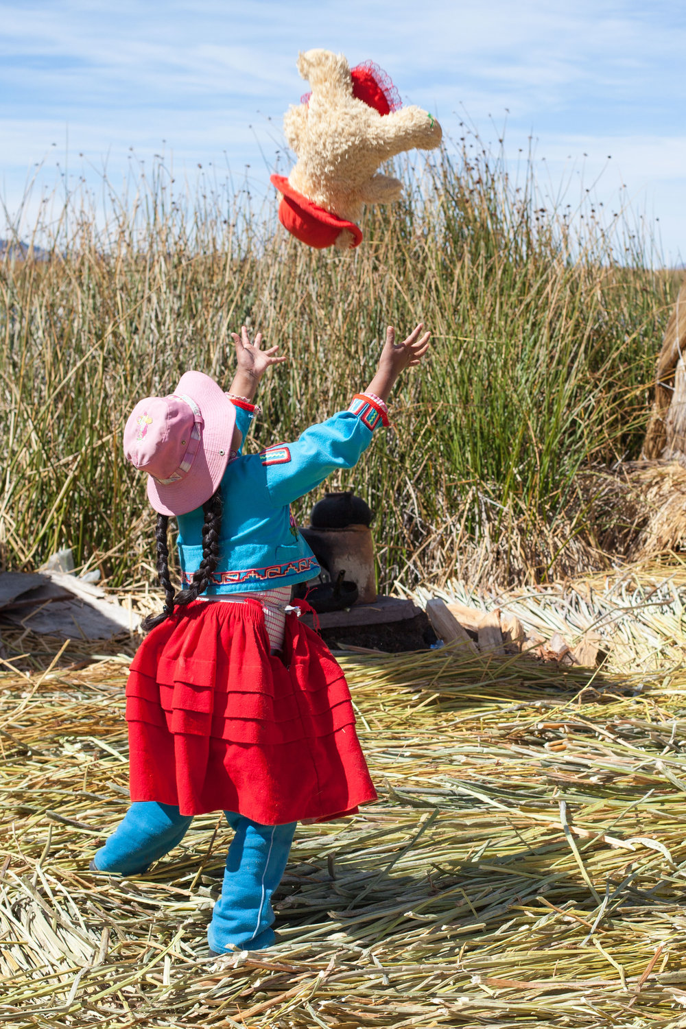 A Peruvian Child in colourful clothing plays on one of the floating reed islands on Lake Titicaca.