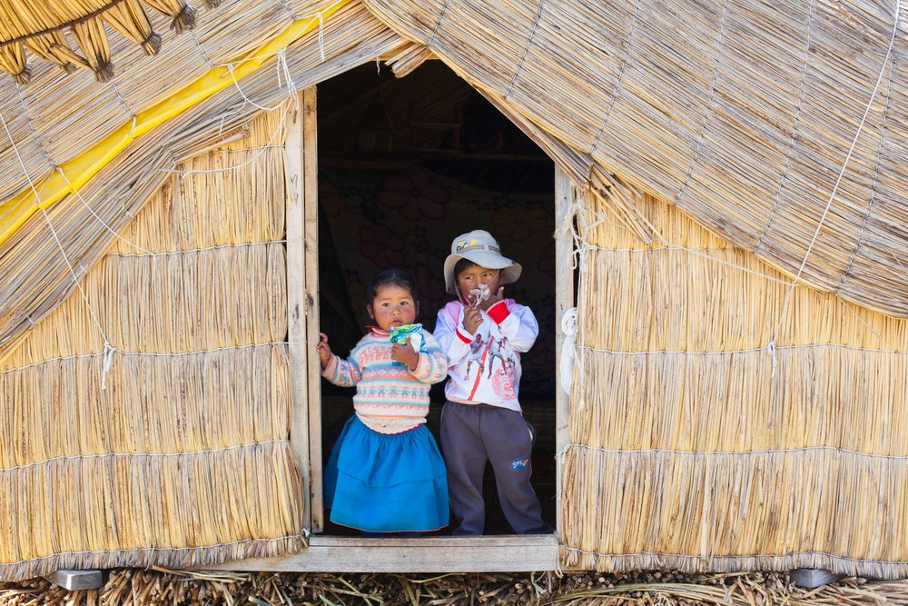 Children living in a reed hut on a island made of reed in Peru.