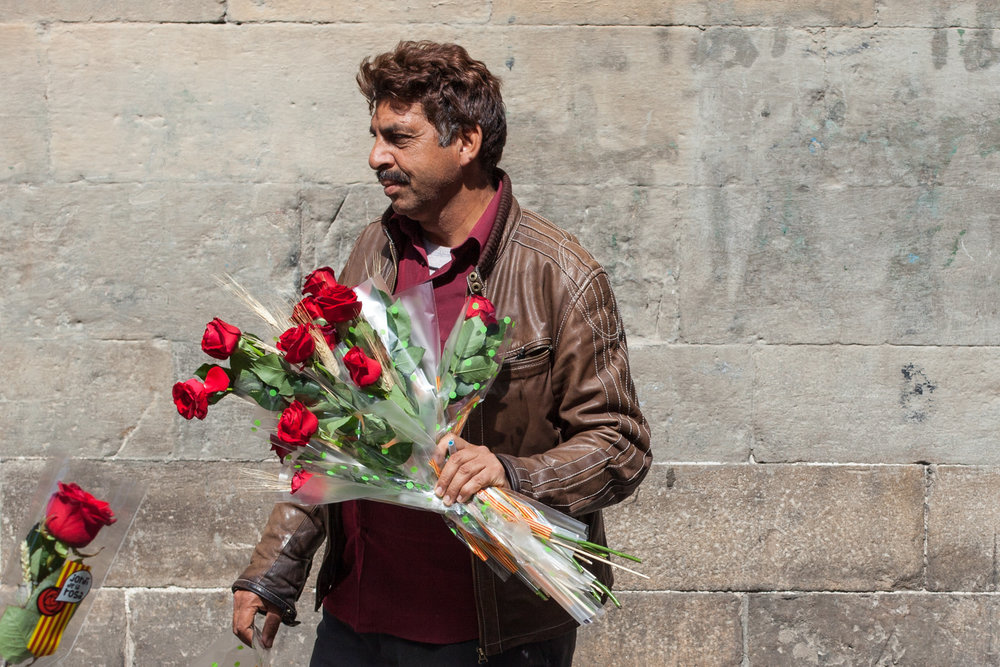 A man sells flowers on the streets of Barcelona.