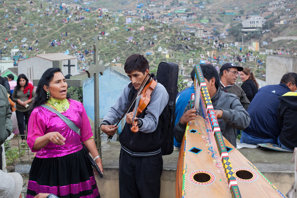 Musicians play for families during Day of the Dead in Lima, Peru.
