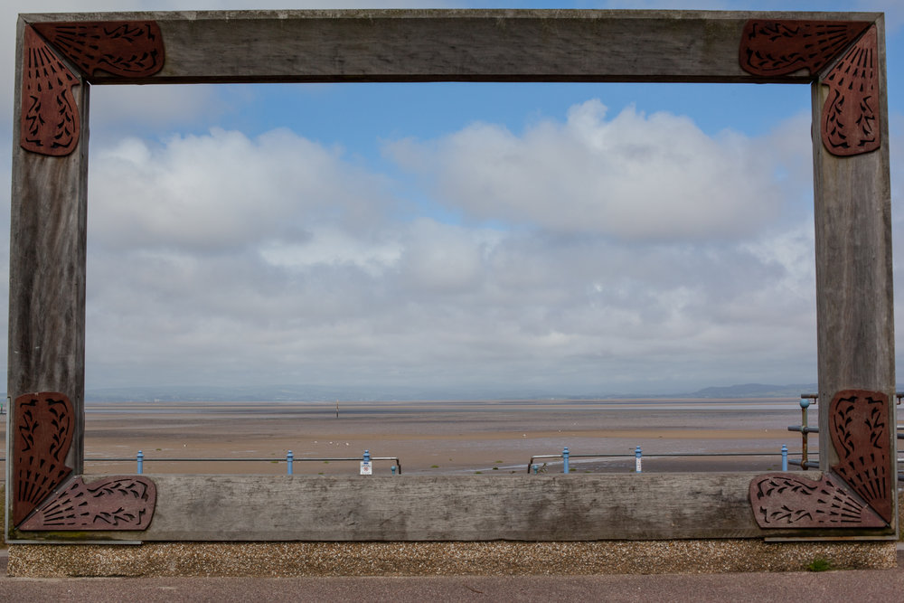 A piece of modern art frames this image looking out to the sea in Morecambe, England.