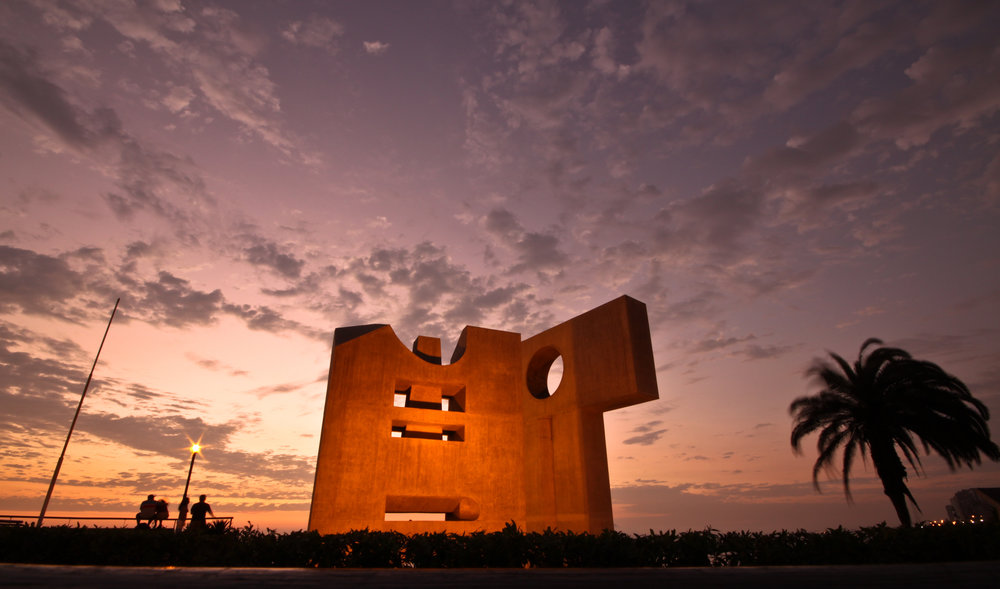 A vivid sun sets over some modern art on the malecon of Miraflores in Lima, Peru.